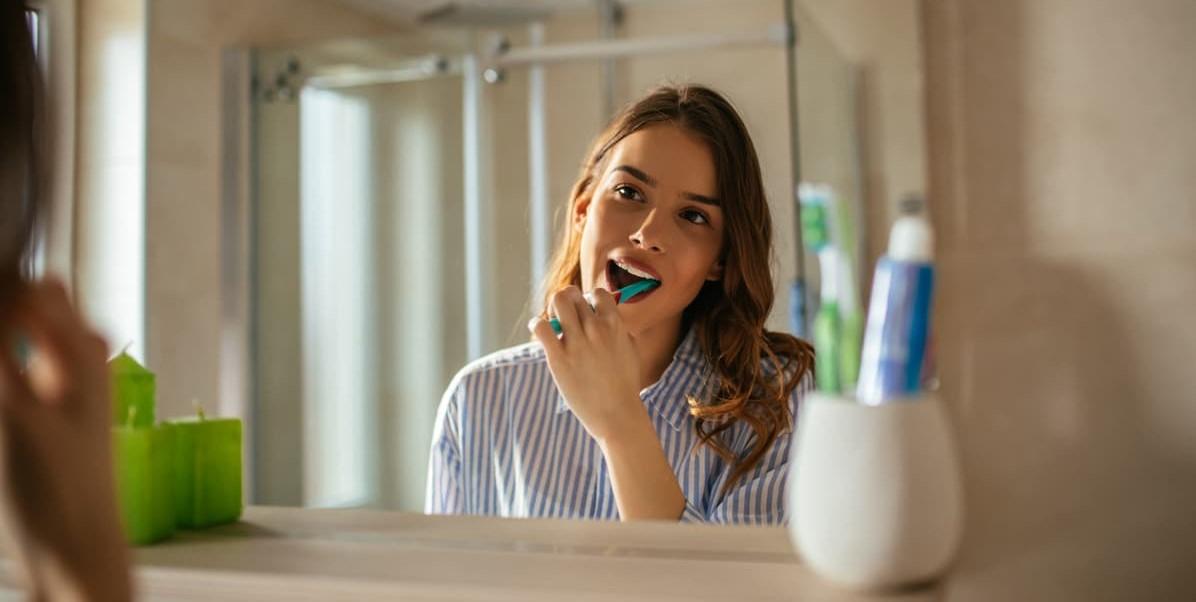 Higiene Bucal. Mulher escova os dentes