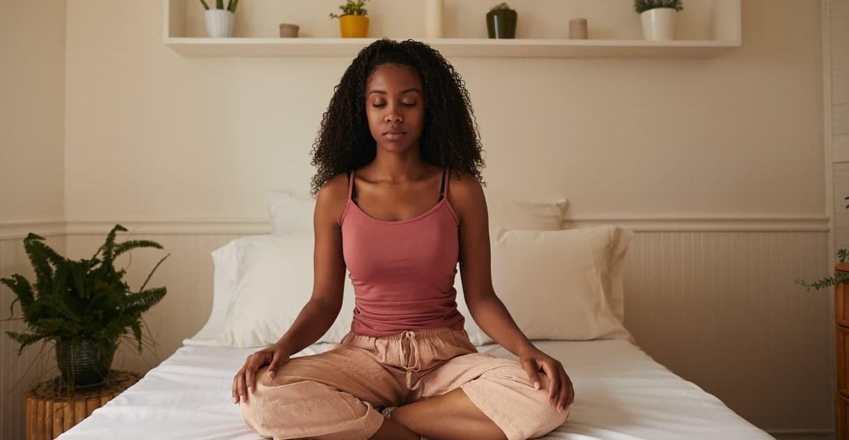 Meditação. Mulher medita na cama
