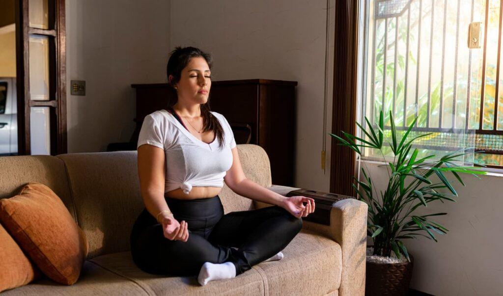 Meditação. Mulher medita no sofá