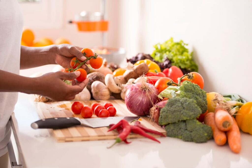 Vitaminas. Mulher corta alimentos