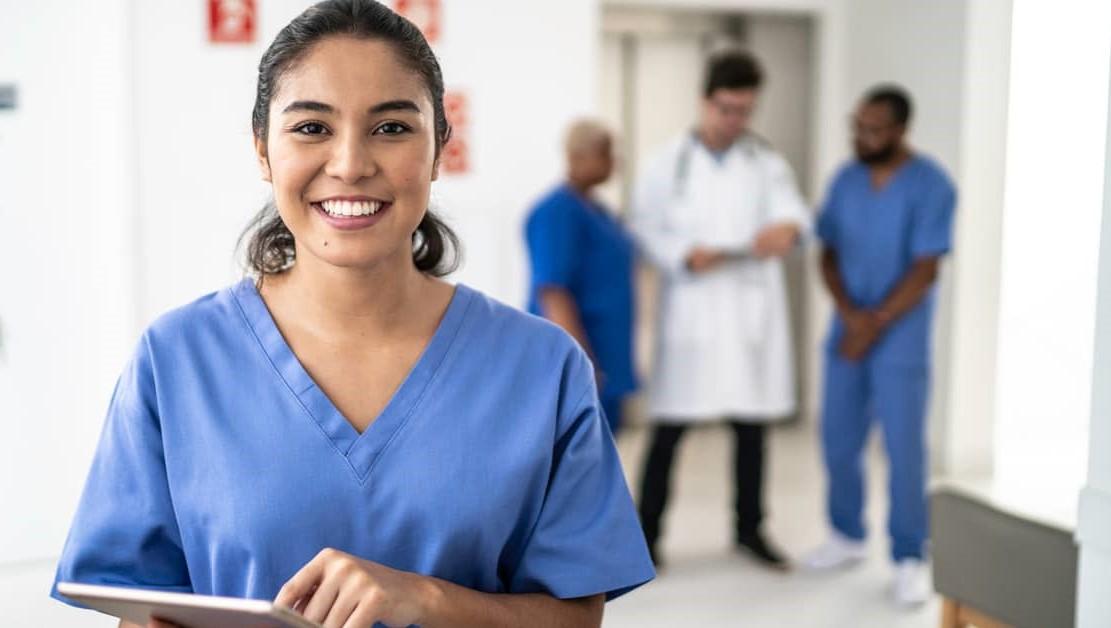 Enfermeira sorrindo com prancheta nas mãos