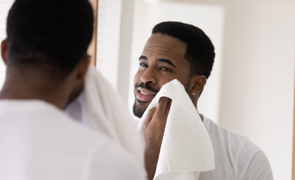 Homem com barba seca o rosto com toalha