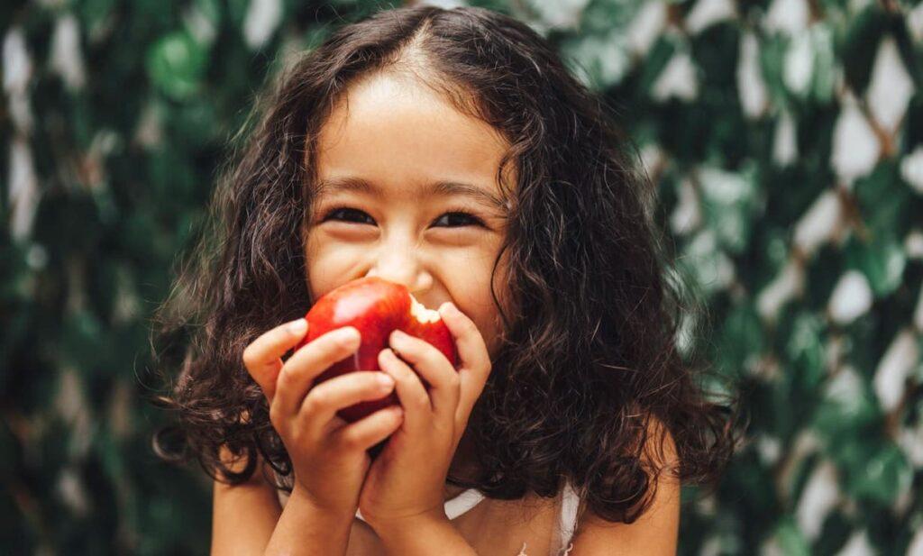 Imunidade infantil, menina come maçã