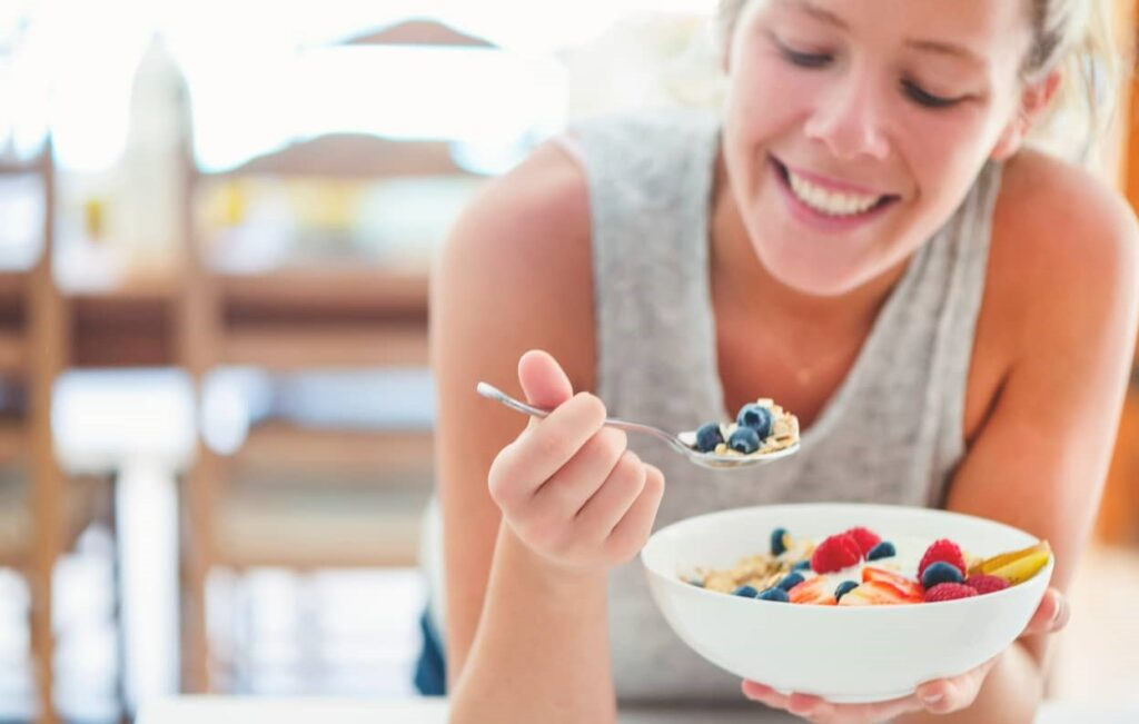 Mulher come prato com variados tipos de alimentos entre eles o mirtilo