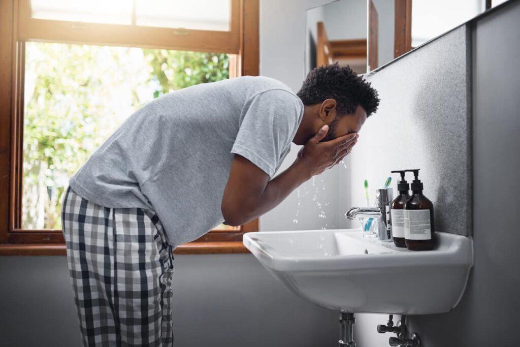 Cuidados com a pele masculina, homem lava o rosto pela manhã