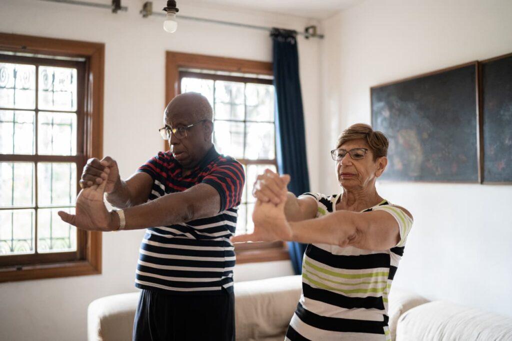 Atividades para idosos, casal idoso alongamento