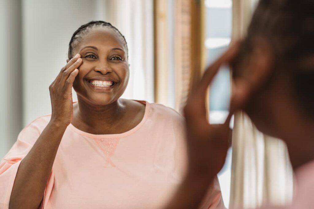 Colágeno verisol, mulher feliz se olha no espelho